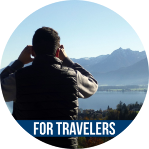 Link to FOR TRAVELERS with image of person taking picture of a mountain view