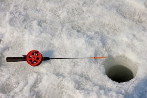 Link to Ice Fishing with image of fishing pole next to hole in ice